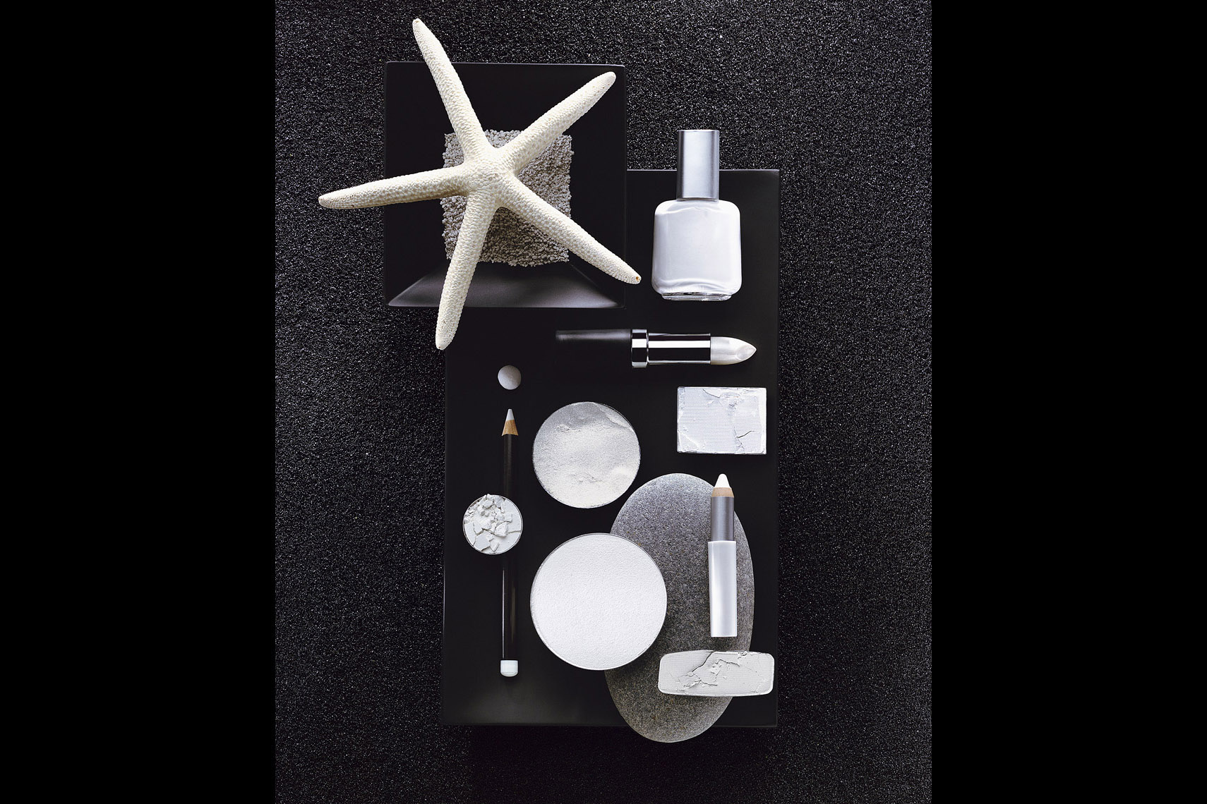 Cosmetics Still Life, White Makeup on Black Sand